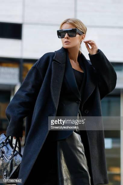Influencer Gitta Banko wearing a black blazer by Saint Laurent a black vegan culotte by Nanushka a black tank top by Zara a long black oversized coat...