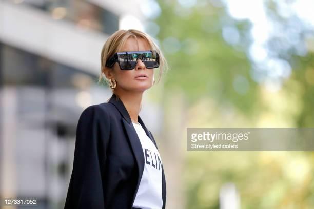 Influencer Gitta Banko wearing a black blazer by Saint Laurent a white tshirt with black logo print by Celine sunglasses by Bottega Veneta and gold...