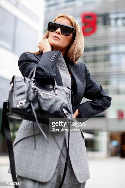 Influencer Gitta Banko wearing a black blazer with white pinstripes and the bottom half with grey glen plaid pattern and matching pants with grey...