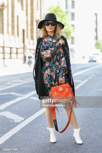 Influencer Gitta Banko wearing a black dress with floral pattern by Zimmermann a black cardigan with a floral stitchery on the back side an orange...