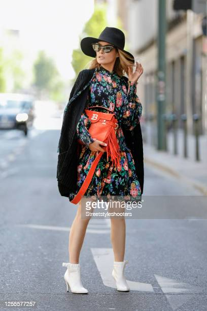 Influencer Gitta Banko, wearing a black dress with floral pattern by Zimmermann, a black cardigan with a floral stitchery on the back side, an orange...