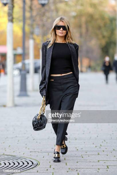 Influencer Gitta Banko wearing a black knitted top by Zara, black pants with cut out details at the hip by Haider Ackermann, black and gold loafers...