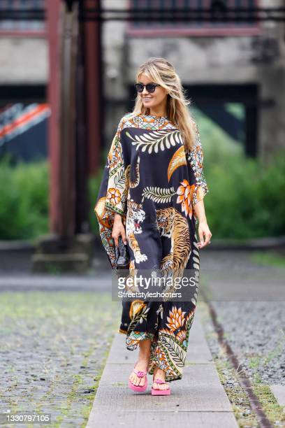 Influencer Gitta Banko wearing a black long kaftan dress with multicolored animal and floral print by Simone Bruns, pink sandals with logo detail by...