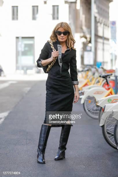Influencer Gitta Banko, wearing a black midi legth pencil dress with collar by Annette Goertz, a black chain pouch bag by Bottega Veneta, black knee...