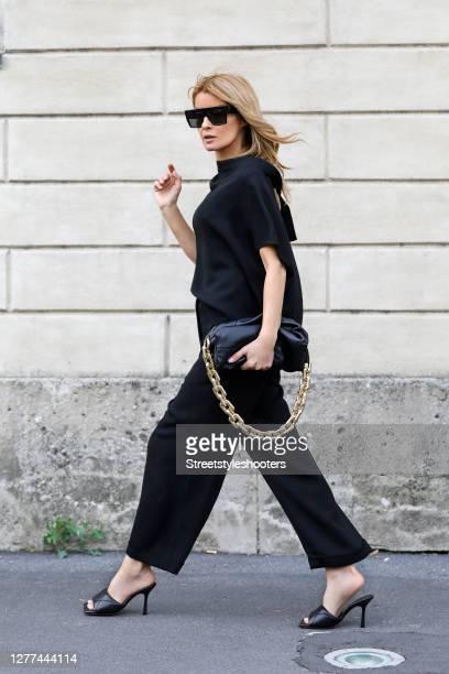 Influencer Gitta Banko, wearing a black top by Annette Goertz, black exposed pants by Annette Goertz, black padded sandals by Bottega Veneta, a black...