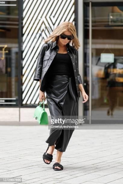 Influencer Gitta Banko wearing a black vegan leather blouse by Nanushka a black vegan leather wrap skirt by Nanushka a black tank top by Zara black...