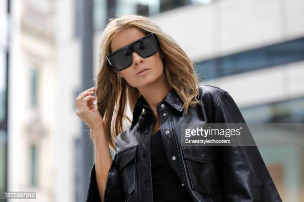 Influencer Gitta Banko wearing a black vegan leather blouse by Nanushka a black tank top by Zara and sunglasses by Celine during a street style...
