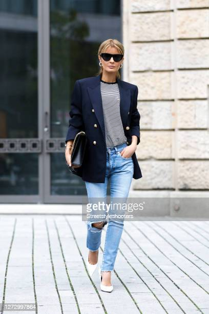 Influencer Gitta Banko wearing a blue and white striped tshirt by Celine and a dark blue blazer by Celine with gold buttons light blue skinny denim...