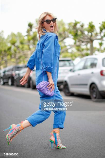 Influencer Gitta Banko, wearing a blue denim jeans overall by One Teaspoon, a purple mini pouch bag by Bottega Veneta, multi colored sandals by...