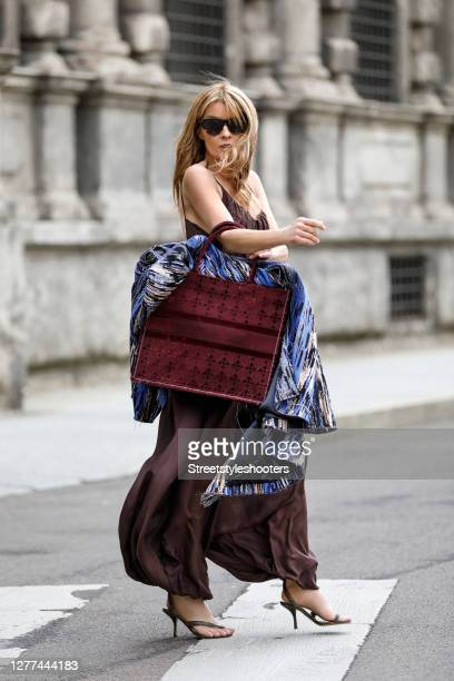 Influencer Gitta Banko, wearing a blue oversize coat with multicolored threats by Irene Luft, a brown silk jumpsuit by Kalita, phyton wrap sandals by...