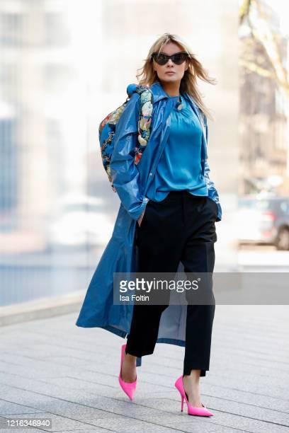 Influencer Gitta Banko wearing a blue raincoat by Rains a blue silk blouse and black pants by Tere Sha pink pumps by Balenciaga a flower printed bag...