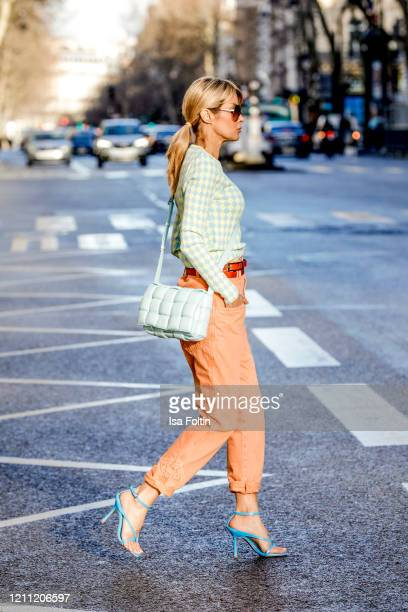 Influencer Gitta Banko wearing a blueyellow colored sweater by Zara orange colored paperbag pants by Isabel Marant a double belt by Boscana blue...