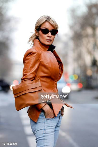 Influencer Gitta Banko wearing a brown tailored leather jacket by Pearl and Rubies a brown leather bag by Boscana a black cashmere sweater by Boscana...
