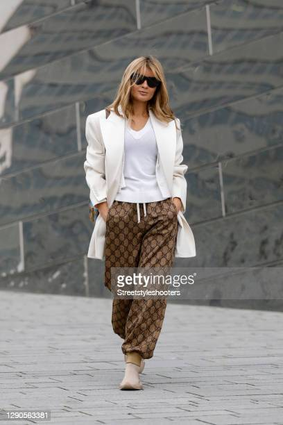 Influencer Gitta Banko wearing a cream colored blazer by Saint Laurent, a white knitted v-neck top and a white cardigan by Dorothee Schumacher, brown...