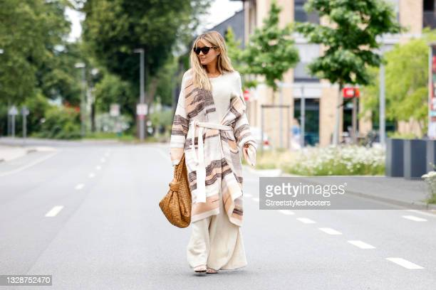 Influencer Gitta Banko wearing a cream colored knitted cashmere maxi dress by Canessa, a long cream colored and brown striped knitted cashmere...