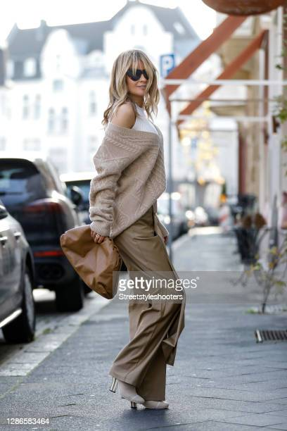 Influencer Gitta Banko wearing a cream colored knitted top by Zara, a beige oversize pullover with braid pattern by The Mercer N.Y., beigefitted...