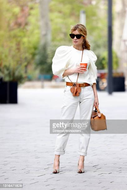 Influencer Gitta Banko wearing a cream colored silk blouse with balloon sleeves by Isabel Marant, cream colored denim jeans pants by Saint Laurent,...