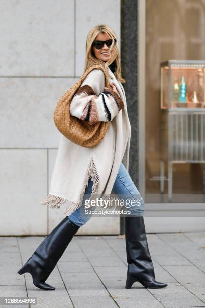 Influencer Gitta Banko wearing a cream colored wool coat with knitted sleeves and fringe details by Beatrice B, light blue denim jeans by AG jeans,...