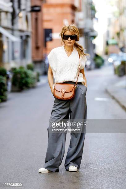 Influencer Gitta Banko, wearing a creme colored knit vest by H&M, grey pants by Zara, a cognac colored bobby bag by Dior, white sneakers by Y3,...
