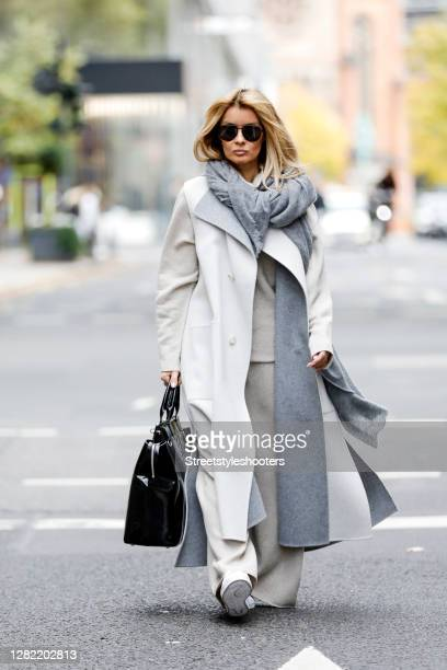 Influencer Gitta Banko, wearing a creme colored turtleneck pullover, creme colored nkit pants, a creme colored long vest and a grey scarf by Issey...