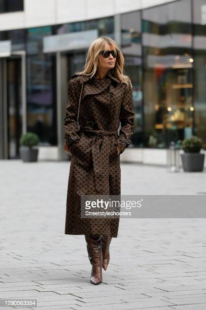 Influencer Gitta Banko wearing a dark brown trenchcoat with 70's triomphe print by Celine, a cognac colored chain bag with gold triomphe details by...