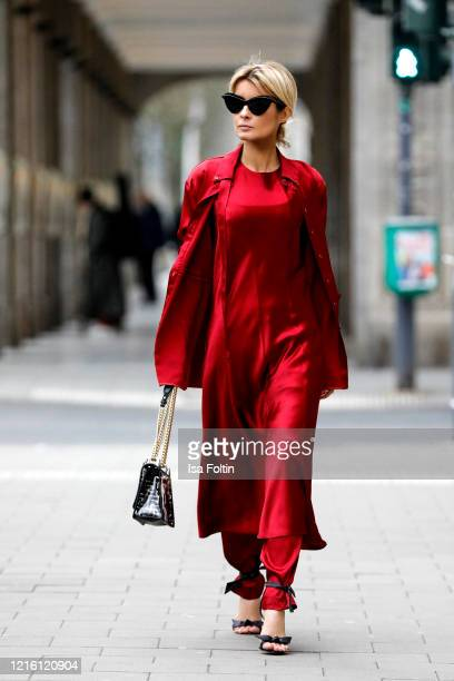 Influencer Gitta Banko, wearing a dress over pants look with a red oversized blouse, a red flared medi dress and red satin pants by Liviana Conti, a...