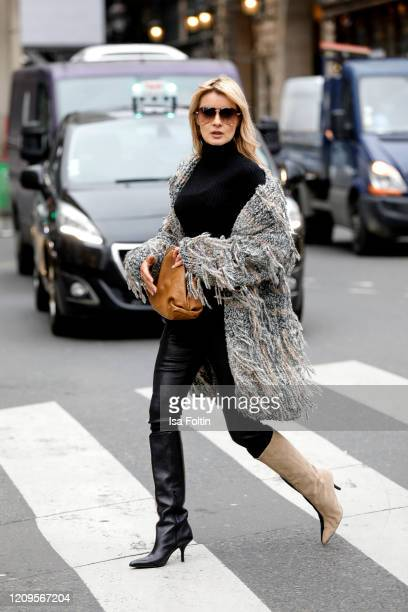 Influencer Gitta Banko, wearing a fringed oversized cardigan and a black turtleneck cashmere sweater by Boscana, black leather pants by Hironae, a...