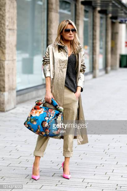 Influencer Gitta Banko wearing a golden coat beige pants and a grey shirt by Annette Goertz a big blue tissue bag with retrostyle flower print by...