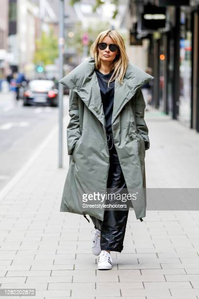 Influencer Gitta Banko, wearing a green coat by Annette Goertz, black down pants and a black shirt by Y3, white sneakers by Adidas and sunglasses by...