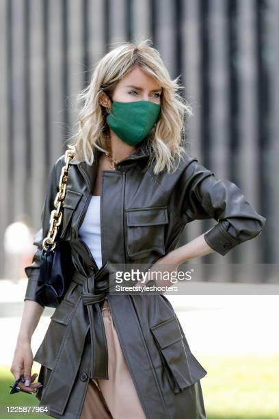 Influencer Gitta Banko, wearing a green face mask by Boscana, a black chain pouch bag by Bottega Veneta, a khaki leather coat by Sundarbay, beige...