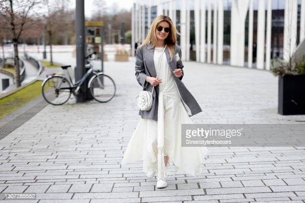 Influencer Gitta Banko wearing a grey blazer with a white lace flower pocket square by Brunello Cucinelli, a long white dress with lace details by...