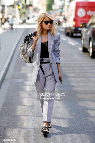 Influencer Gitta Banko wearing a grey blazer with matching high waist pants by Isabel Marant a black tank top by iHeart a snake necklace by...