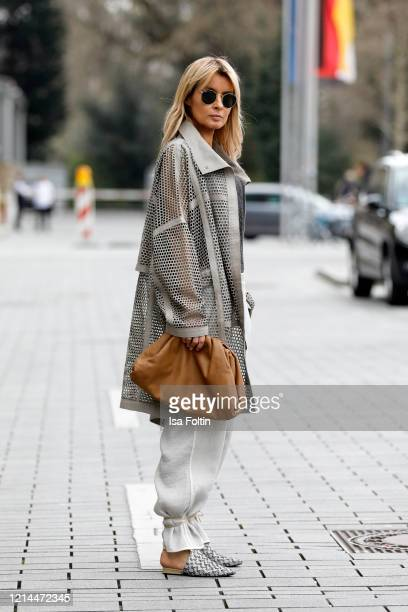 Influencer Gitta Banko, wearing a grey leather coat with cut out look, beige pants and a dark grey shirt by Annette Goertz, a caramel colored pouch...