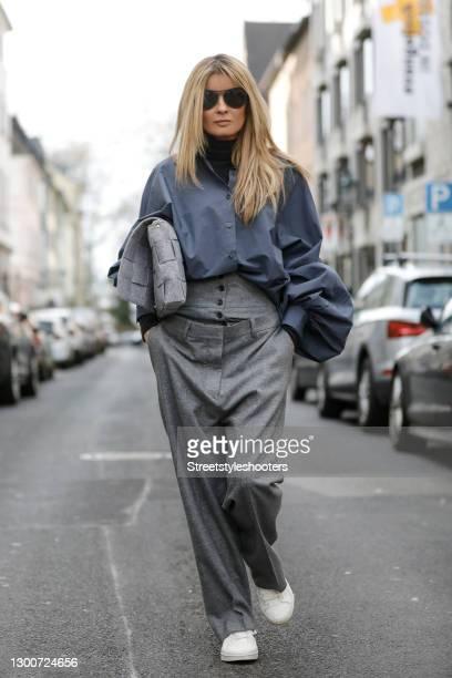 Influencer Gitta Banko wearing a grey oversize blouse with bat sleeves by SoSUE, light grey double waist pants by Boscana x Gitta Banko, white...