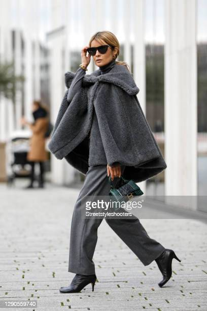 Influencer Gitta Banko wearing a grey teddy cape by Max Mara, grey frame pants with front creases and zipper pockets by Brunello Cucinelli, a grey...