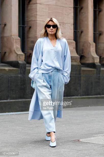 Influencer Gitta Banko, wearing a jeans by Magda Butrym, a pastel blue pullover and a pastel blue cardigan by t7berlin, a topaz colored padded...