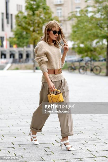 Influencer Gitta Banko wearing a knitted beige pullover with multicolored sequin by Loewe a brown belt with gold details by Loewe a yellow mini...