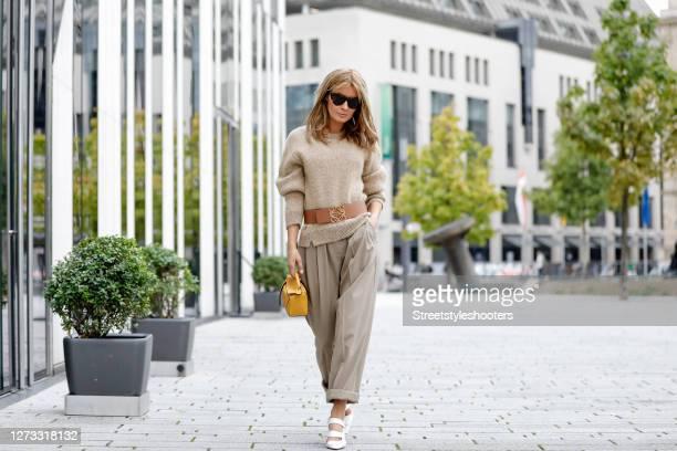 Influencer Gitta Banko wearing a knitted beige pullover with multicolored sequin by Loewe, a brown belt with gold details by Loewe, a yellow mini...