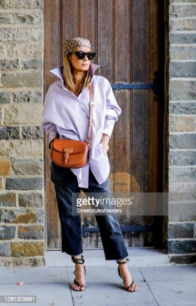 Influencer Gitta Banko, wearing a lavandel colored oversize blouse by Boscana, a black slouchy Jeans by Nili Lotan, phyton wrap sandals by Bottega...