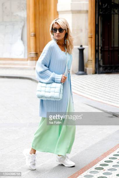 Influencer Gitta Banko, wearing a light blue oversize cardigan by Boscana, a light green-blue silk dress by Delicate Love, a brooch and sneakers by...