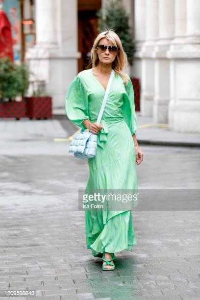 Influencer Gitta Banko, wearing a light green-blue silk wrap maxi dress by Delicate Love, a topas colored padded cassette bag by Bottega Veneta, neon...