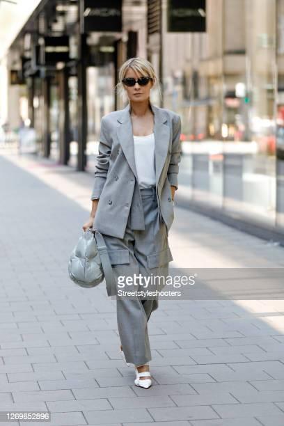 Influencer Gitta Banko wearing a light grey blazer and matching pants by Annette Goertz, white bv point pumps by Bottega Veneta, sunglasses by Mykita...