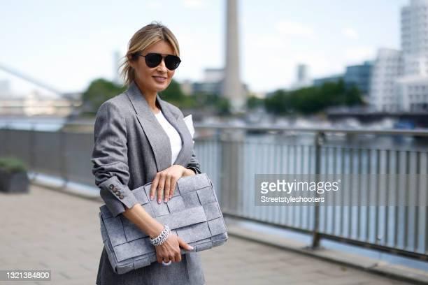 Influencer Gitta Banko wearing a light grey blazer by Brunello Cucinelli, a long light grey pleated skirt by Brunello Cucinelli, a white shirt by...