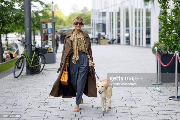 Influencer Gitta Banko wearing a light olive green blouse with gold polka dots by Saint Laurent, a long brown trenchcoat by Saint Laurent, dark grey...