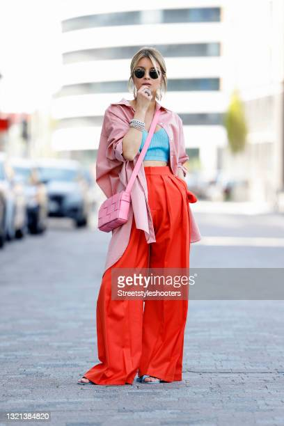 Influencer Gitta Banko wearing a light pink oversize blouse by Gitta Banko, a aqua blue wool and silk bralette by Boscana, red marlene pants by...