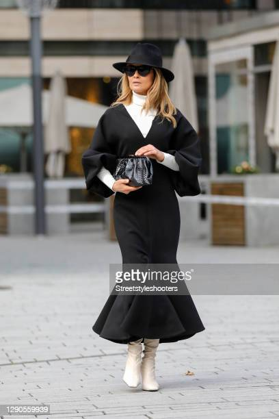 Influencer Gitta Banko wearing a long black dress with balloon sleeves by Valentino, a cream colored turtleneck pullover by Saint Laurent, a black...