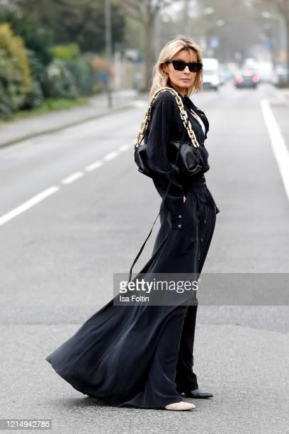 Influencer Gitta Banko, wearing a long black silk dress by Jacob Lee, a white tanktop by Zara, a chain pouch bag by Bottega Veneta, two tone boots by...