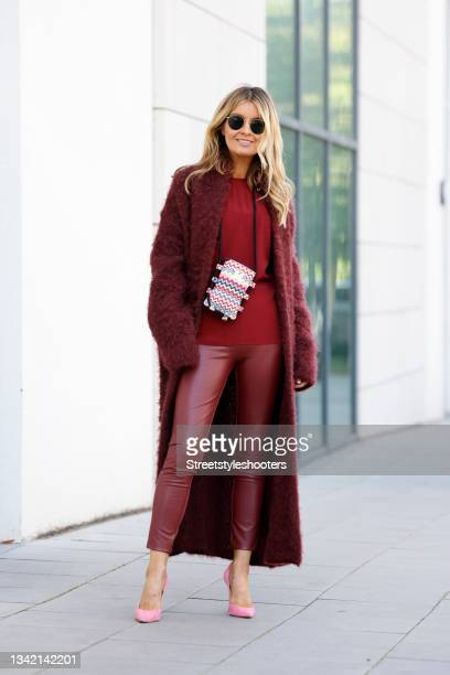 Influencer Gitta Banko wearing a long burgundy colored fuzzy coat by Roberto Collina, a burgundy colored blouse by M Missoni, a small multicolored...