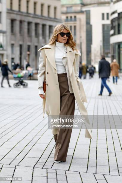 Influencer Gitta Banko wearing a long cream colored vest by Nanushka, mocha colored flared pants with front creases by Nanushka, a cream colored...