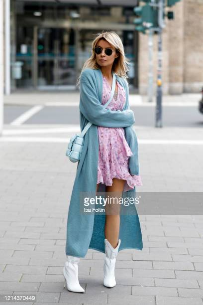 Influencer Gitta Banko wearing a long knit blue cardigan by The Mercer NY a rose colored dress by Iro white leather boots by Malone Souliers a topaz...
